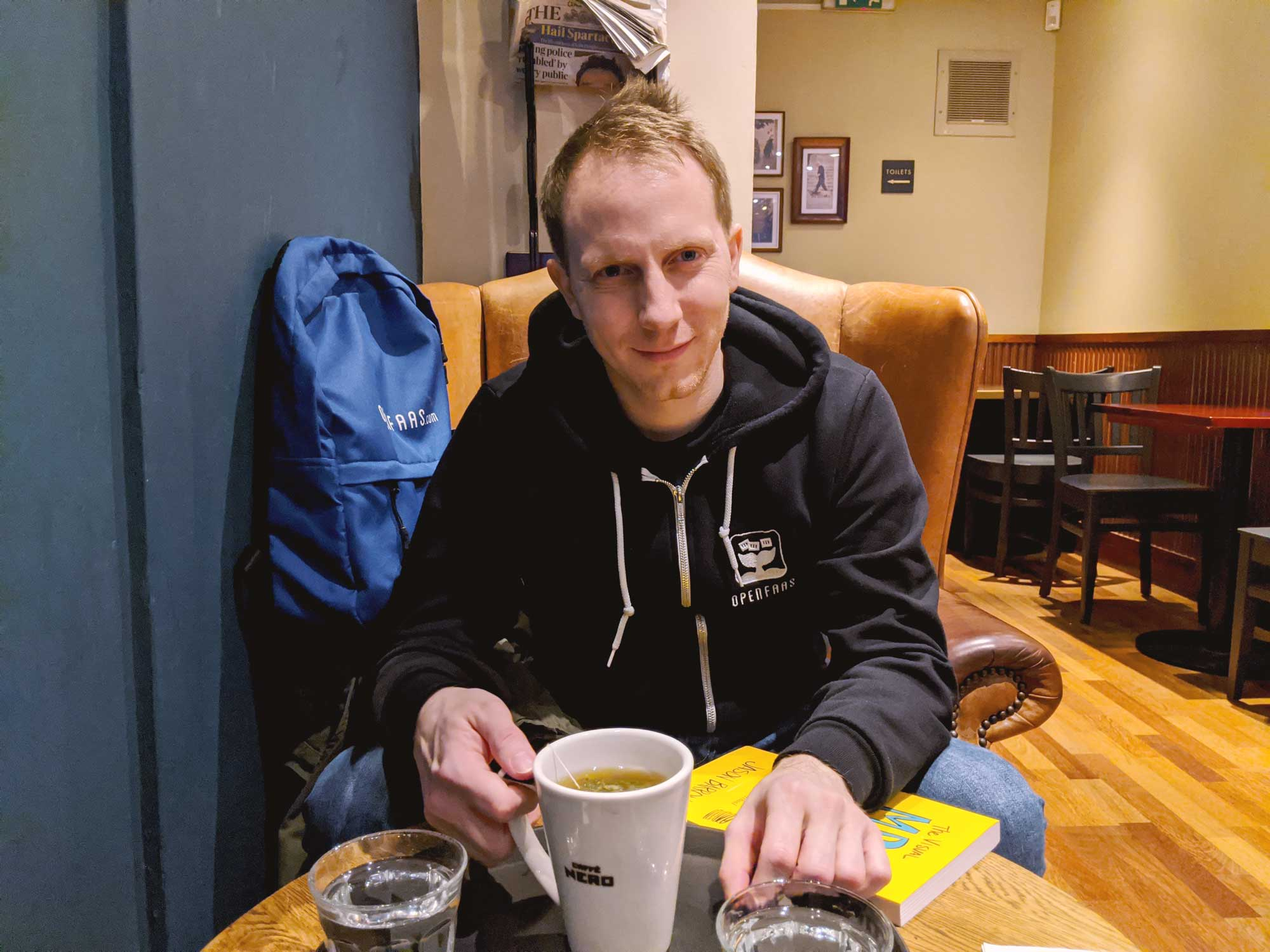 Photo of Alex Ellis at a cozy coffee shop, wearing an OpenFaaS branded hoodie.