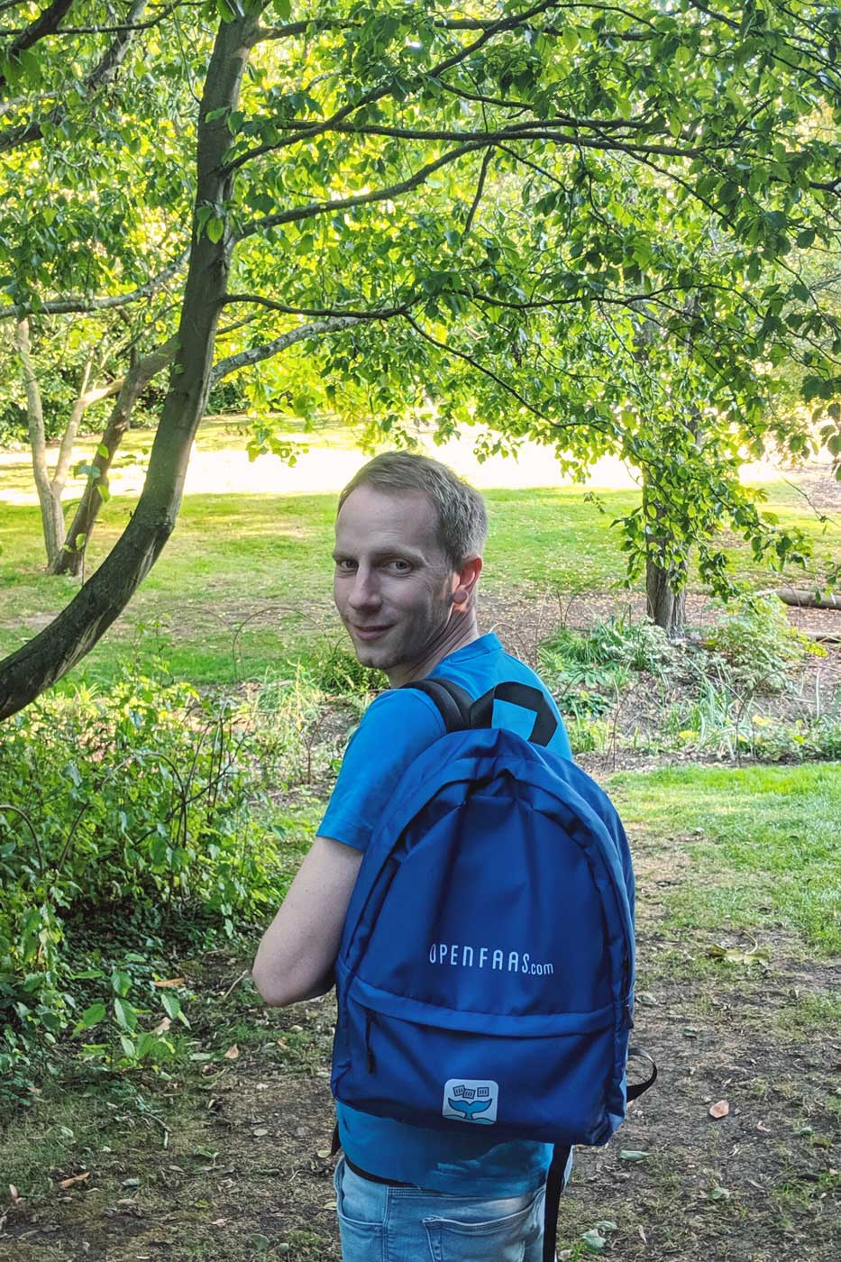 Photo of Alex Ellis surrounded by greenery, wearing an OpenFaaS branded backpack.