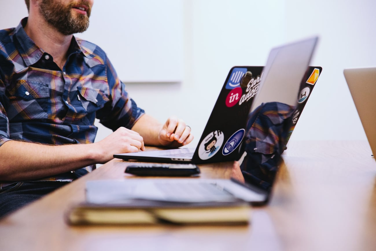Photo of a male developer next to his laptop full of stickers.